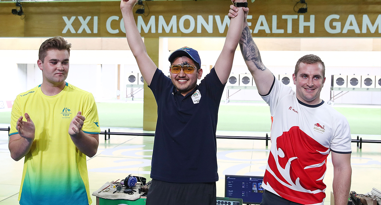 Sergei Evglevski of Australia, gold medalist Anish of India and bronze medalist Sam Gowin of England celebrate after the 25m Rapid Fire Pistol Men's Finals