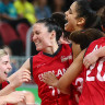England players celebrate their shock win over Canada in the women's basketball semifinal.
